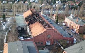 Bild der abgebrannten Lagerhalle in Berlin. Links unten sind die Reste des DBM-Autos unter einer Plane zu sehen.