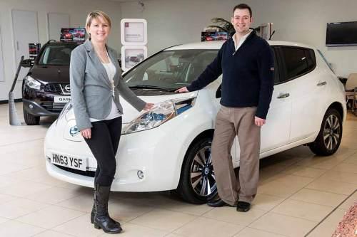 Die Besitzer des 100.000sten Nissan Leaf vor ihrem neuen Auto.